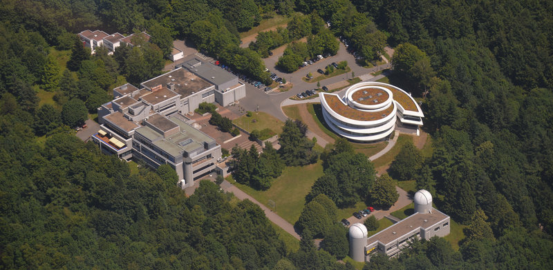 Max Planck Institute for Astronomy (MPIA) and Haus der Astronomie (HdA; Heidelberg's Center for Astronomy Education and Outreach) on the Königstuhl Mountain in Heidelberg. Bottom left:  Elsässer Laboratory (MPIA) with two telescope domes; center right: galaxy-shaped HdA building, center left:  MPIA main building.