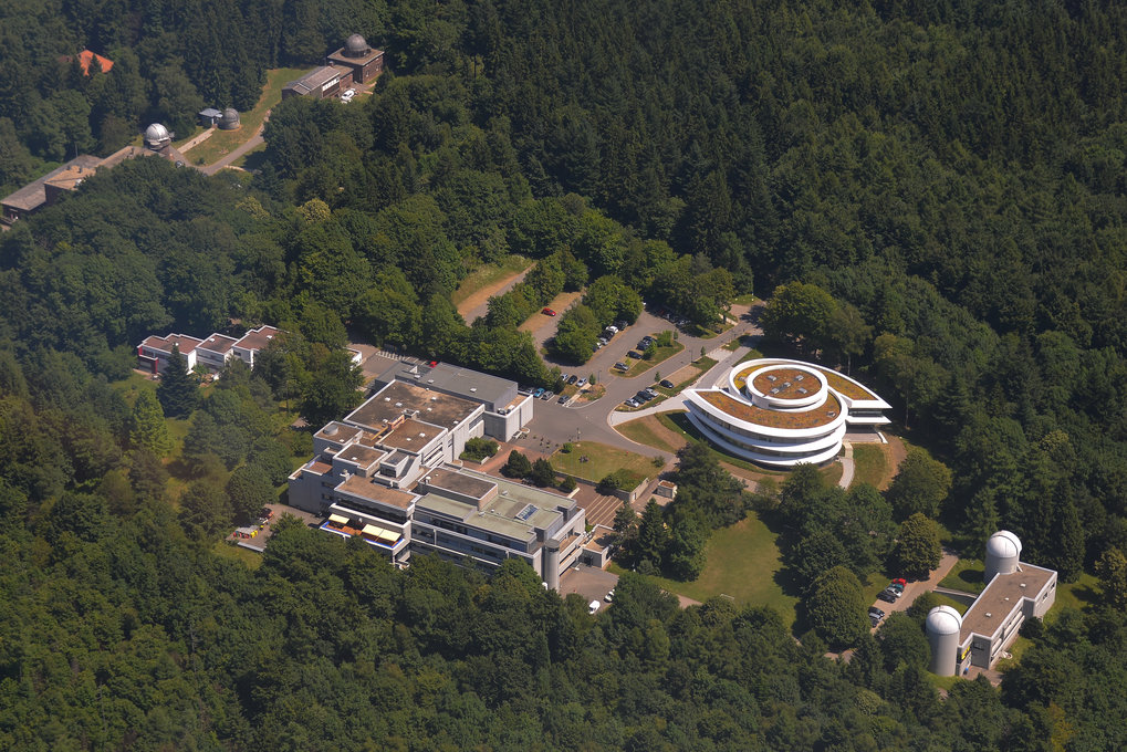 Max Planck Institute for Astronomy (MPIA), Haus der Astronomie (HdA; Heidelberg's Center for Astronomy Education and Outreach) and Landessternwarte on the Königstuhl Mountain in Heidelberg. Bottom right, the two domes of the Elsässer Laboratory (MPIA), center right the galaxy-shaped HdA building, center left the MPIA main building, and top left the buildings and domes of the Landessternwarte. Image: Sebastian Egner