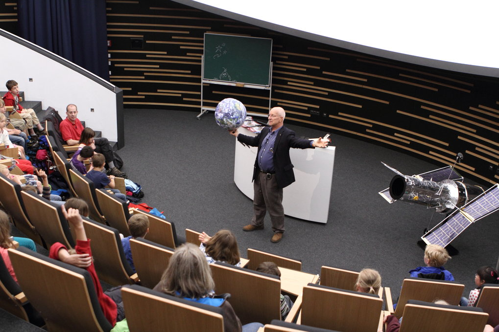 Event for elementary school children in the Klaus Tschira Auditorium of Haus der Astronomie (our central lecture hall seating 100, and featuring a digital planetarium system): ESA astronaut Dr. Claude Nicollier demonstrates length scales in our cosmic neighbourhood using a UNAWE earth ball. The event was part of HdA's